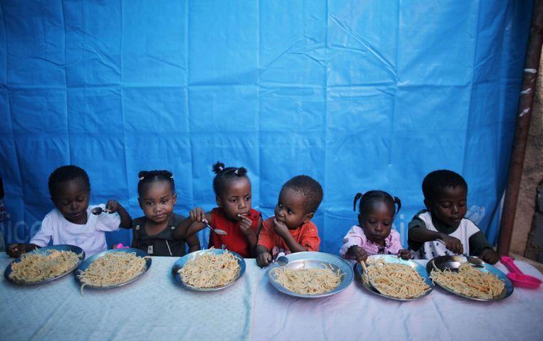 Kinderen in een tehuis in Port-au-Prince, twee weken na de aardbeving. Beeld Reuters