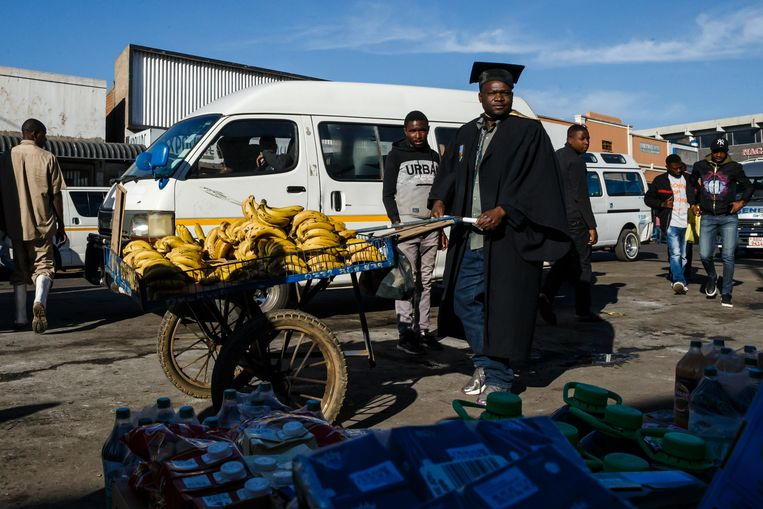 Abel Kapodogo verkoopt bananen op de markt in Harare. Uit protest tegen de armoede in zijn land doet hij dat in de toga die hij zeven jaar geleden bij zijn afstuderen als socioloog droeg. Hij is sindsdien werkloos. Beeld AFP