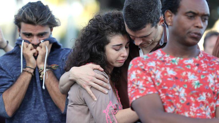 Mensen huilen op de plek waar de aanslag is gepleegd. Beeld afp