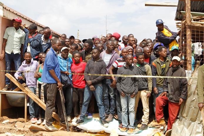 Kenianen kijken toe hoe het reddingsteam in de puinhoop zoekt naar slachtoffers.