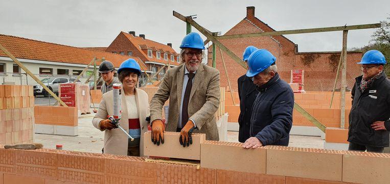 Schepen Staf Willemsen legt een symbolische steen voor de sociale woningen onder het goedkeurende oog van gedeputeerde Kathleen Helsen en rijkswachter op rust Roger Swannet.