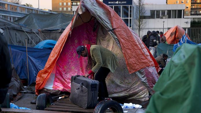 Een uitgeprocedeerde asielzoeker pakt zijn spullen in in het tentenkamp in Osdorp