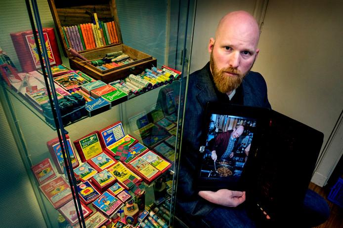 Koen Makkelie met een foto van zijn vader Joop bij de vitrinekast met oud vuurwerk in het huis van zijn vader.