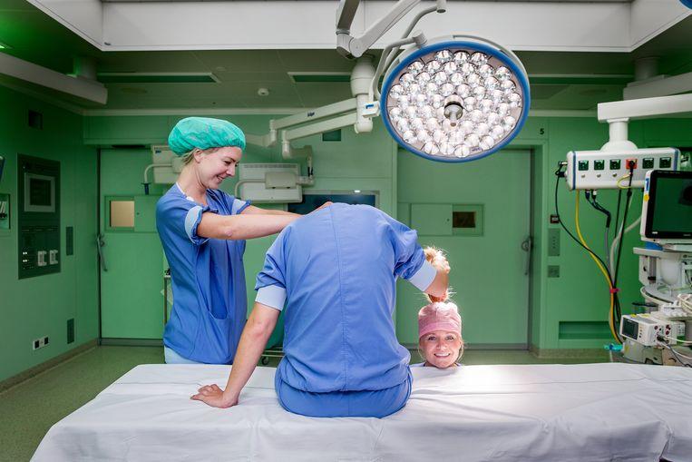 Sonja duwt het hoofd van Amy naar beneden, zodat het lijkt alsof  haar hoofd eraf is en op de operatietafel ligt.  Beeld Jean-Pierre Jans