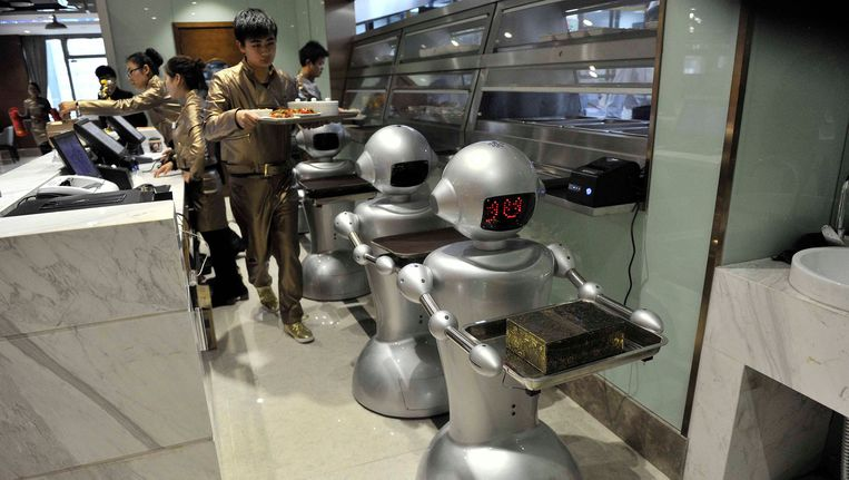 Bij een restaurant in de Chinese stad Hefei verzorgen robots al een groot deel van de service aan de klanten. De eters worden door in totaal 30 robots verwelkomd en bediend, en ook hebben ze taken in de keuken. Het restaurant is met 1300 vierkante meter het grootste robotrestaurant in China. Voor Nederland toekomstmuziek, of niet? Beeld REUTERS
