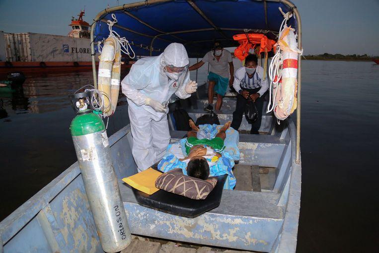 Een 11-jarige coronapatiënt wordt over de Amazonerivier vervoerd naar een ziekenhuis.  Beeld AFP