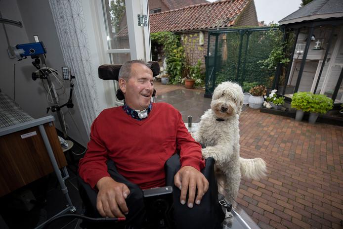 Jan van Hoof in zijn kamer, met zijn hond.