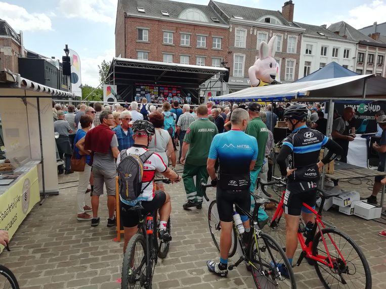 Wielerfans volgen de ploegenvoorstelling op het podium, naast de kraampjes van Fiesta Europa.