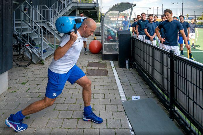 HC Den Bosch-trainer Eric Verboom doet naast het veld een krachtoefening voor aan zijn spelers.