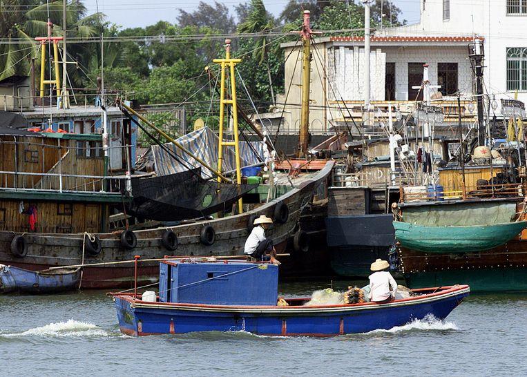 Chinese vissers varen met een motorboot langs enkele vissersboten in Tanmen. Beeld anp