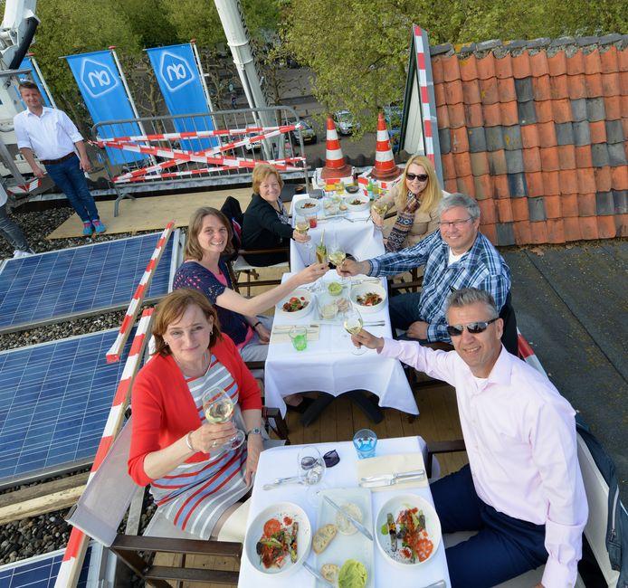Veilig boven gekomen, toosten de geluksvogels op hun prijs: een exclusief diner op het dak van de Albert Heijn in Houten.