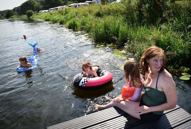 Gasten van De Roos zwemmen in de Vecht. De angst van bezoekers is dat het pure De Roos het pad van de commercie zal opgaan. Beeld Marcel van den Bergh / de Volkskrant