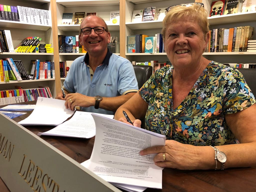 Leo en Marjan Middelhoek van boekhandel Marjan Houtman in Puttershoek tekenen het contract voor overname van hun zaak.