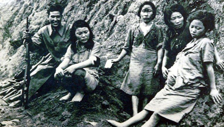 Een Japanse militair poseert met enkele Koreaanse troostmeisjes. Beeld ChosunIlbo