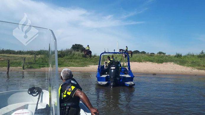 Politie te water krijgt hulp van politie te paard langs de Maas bij Ammerzoden.
