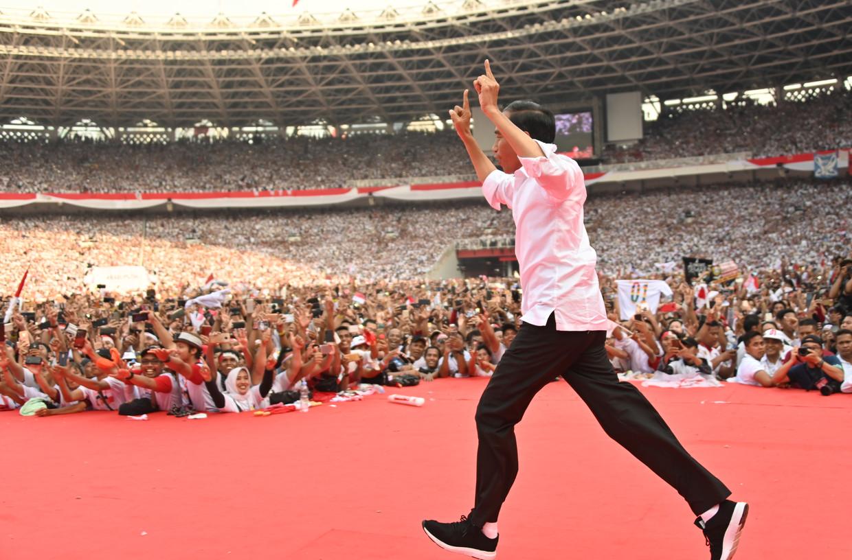 De zittende president Joko Widowo komt het podium op voor zijn verkiezingsbijeenkomst in het stadion Gelora Bung Karno in Jakarta, 13 april.  Beeld AFP