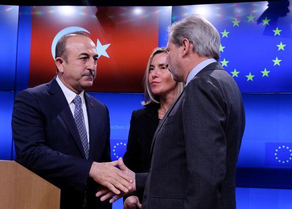 De Turkse minister van Buitenlandse Zaken Mevlut Cavusoglu en de Eurocommissaris voor Uitbreiding Johannes Hahn schudden elkaar de hand. De Europese minister van Buitenlandse Zaken Federica Mogherini kijkt intussen toe.