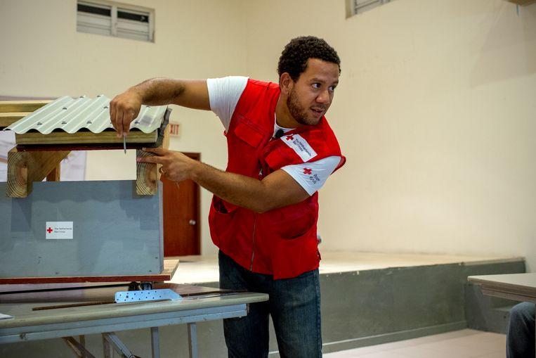 Een Rode Kruis-medewerker leert bewoners hoe zij daken stevig moeten bevestigen. Beeld Rode Kruis