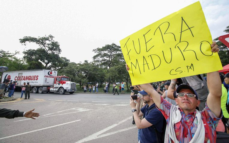 Mensen betogen tegen president Nicolas Maduro die de hulpgoederen voorlopig niet wil doorlaten.