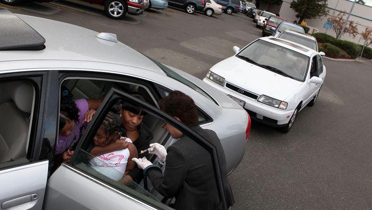 Ouders staan in San Pablo in Californië in de rij bij een drive-in dokterskliniek om hun kinderen tegen de groep te laten inenten. Beeld afp