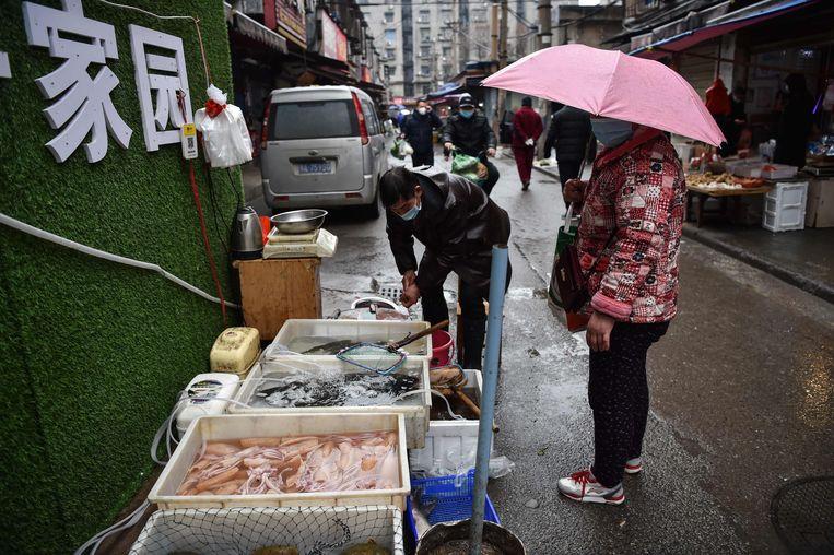 Visverkopers op de markt in Wuhan waar begin januari het nieuwe coronavirus werd ontdekt.  Beeld AFP