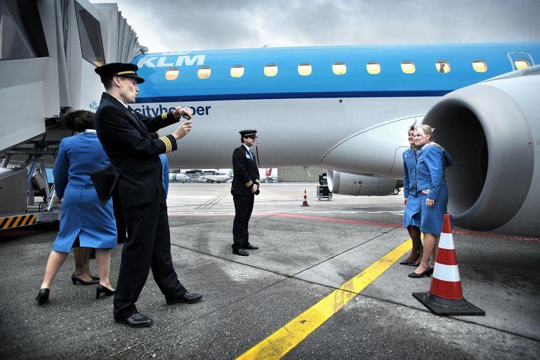 Piloten en stewardessen maken foto's van elkaar bij het toestel van Embraer. Beeld Joost van den Broek / de Volkskrant