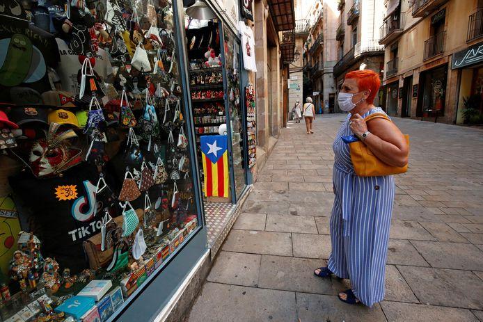 Een vrouw voor een etalage vol mondkapjes in een rustig Barcelona.