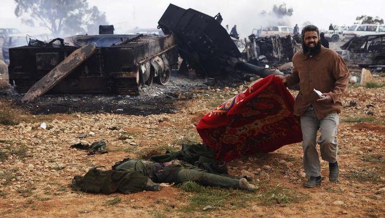 Een man bedekt de lichamen van wat volgens inwoners van Benghazi soldaten van Kadhafi zijn, omgekomen bij een Frans bombardement. Beeld reuters