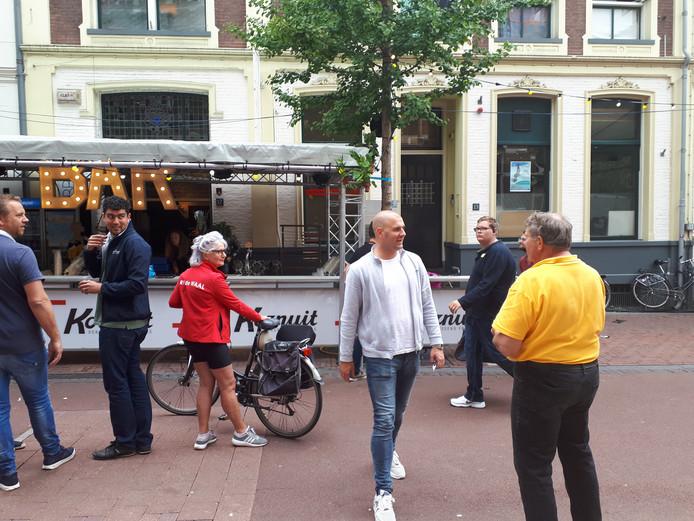 Hans Holland (met geel shirt) klaagt zijn nood over de Vierdaagsebar, pal voor zijn kringloopwinkel Habbekrats.