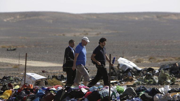 Russische onderzoekers lopen langs bagage en ander materiaal van het neergestorte vliegtuig. Beeld AP