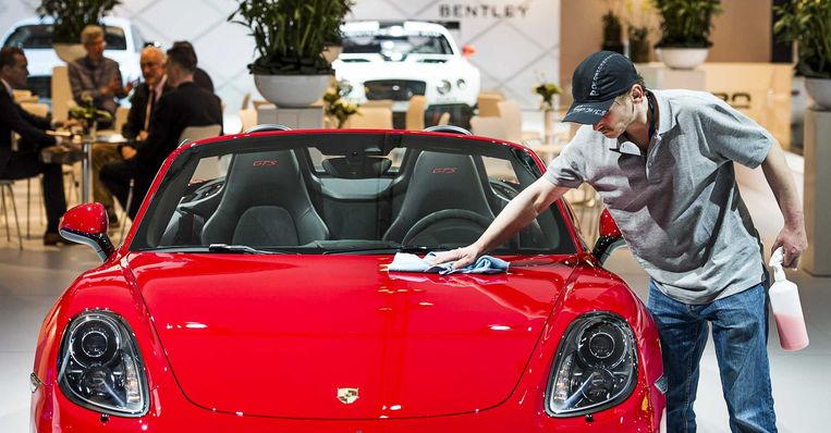 Een Porsche wordt opgepoetst door een medewerker op de AutoRAI. Beeld anp