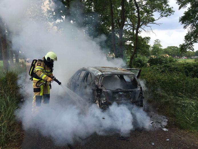 De brandweer blust de brandende wagen.