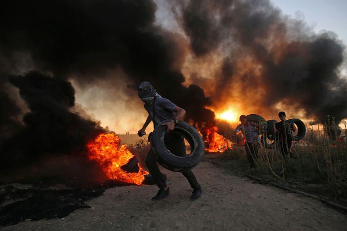 Palestijnse betogers dragen autobanden naar een al brandende stapel tijdens een confrontatie met het Israëlische leger in de Gazastrook.