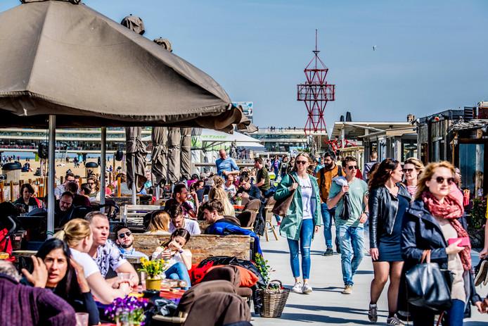 Mensen genieten van het mooie weer op het strand van Scheveningen op de eerste warme lentedag van vorig jaar.