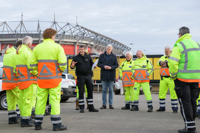 Freddy Korte (zwarte trui links) doet de briefing van zijn verkeersregelaars voor de wedstrijd FC Twente - AZ. Rechts van hem Tweede Kamerlid Chris van Dam die een avond met hem meeloopt.