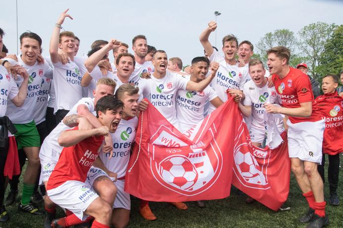 De selectie van Noordwijk viert het kampioenschap in de derde divisie. Vooraan, in het rode shirt, Gouwenaar Thomas Reynaers.