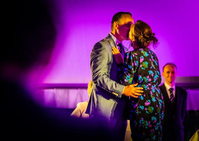 De nieuwe burgemeester Bram van Hemmen krijgt zijn ambtsketen door zijn vrouw omgehangen, gevolgd door een kus.