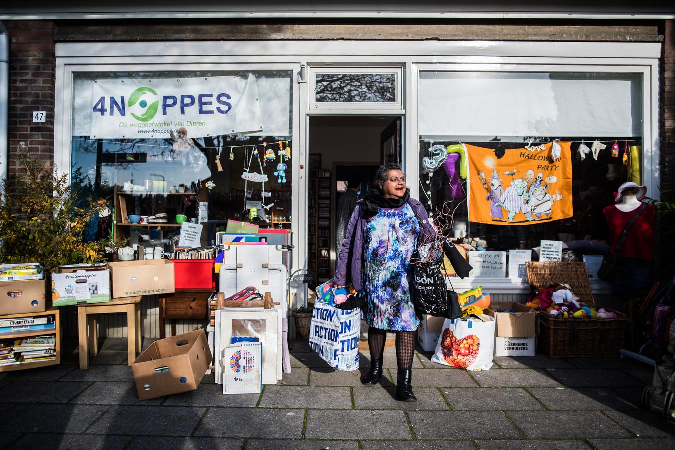 Een bezoekster verlaat met volle tassen weggeefwinkel 4Noppes in Dieren.