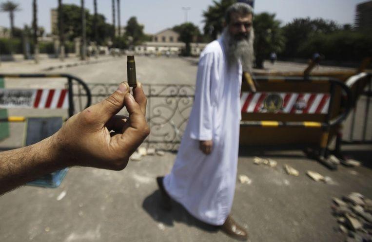 Een aanhanger van president Morsi laat een kogelhuls zien na een nacht van clashes met tegenstanders van Morsi. Beeld null