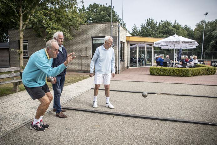 Frans Draaijer (links) werpt een jeu-de-boulesbal op de nieuwe banen bij tennisclub de Acehof in Tubbergen, met naast hem jeu-de-boulespionier in Tubbergen Jan Fortkamp (midden) en bestuurslid Jos Ypma.