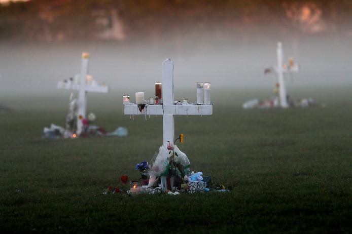 Herinneringskruisen met bloemen en kaarsen staan op het grasveld bij de Marjory Stoneman Douglas High School, voor elke gedode leerling één.