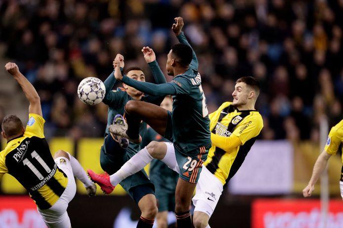 Bryan Linssen en Matus Bero voor Vitesse in gevecht met Ryan Gravenberch van Ajax.