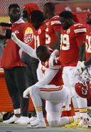 Alex Okafor knielt en steekt zijn arm in de lucht vlak voor de start van het nieuwe NFL-seizoen.