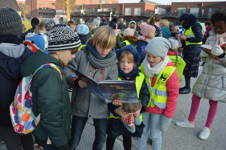 Enkele kinderen lezen een verhaaltje aan elkaar voor in de voorleesslinger.
