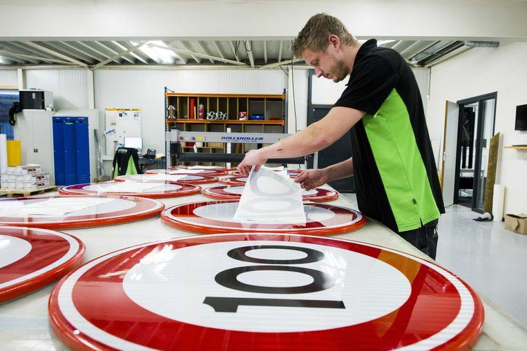 Bij Visser print & sign in Assen worden nieuwe verkeersborden voor de maximale snelheid beplakt.