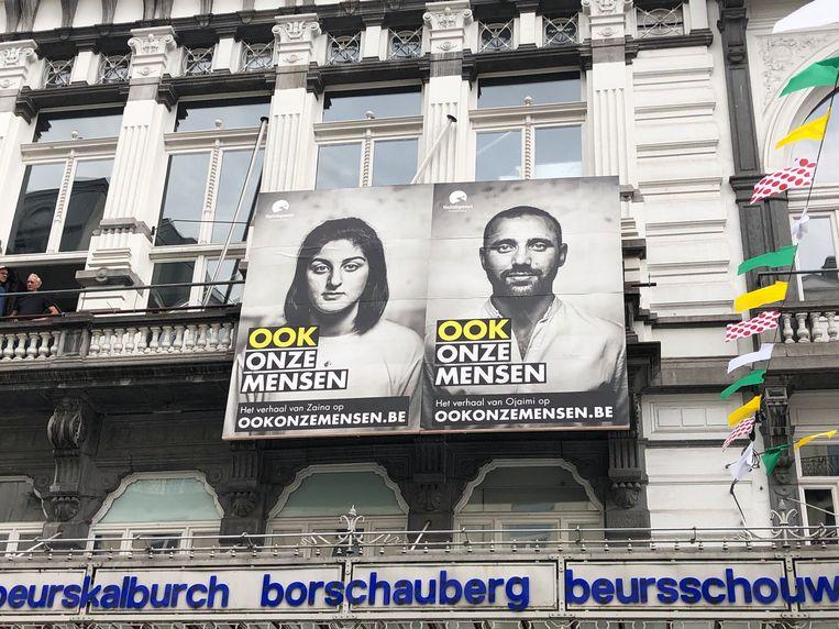 De grote affiches op de gevel van de Beursschouwburg tonen portretten van vier vluchtelingen die in België neerstreken en hulp kregen van Vluchtelingenwerk Vlaanderen.