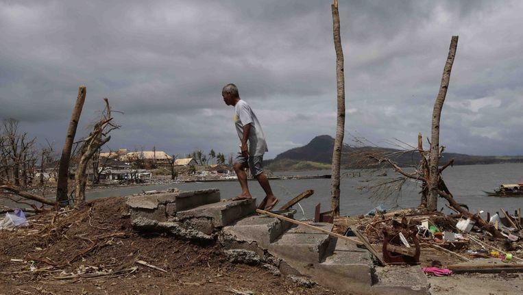 Een man loopt over de restanten van een trap in de verwoeste stad Tacloban. Beeld ap