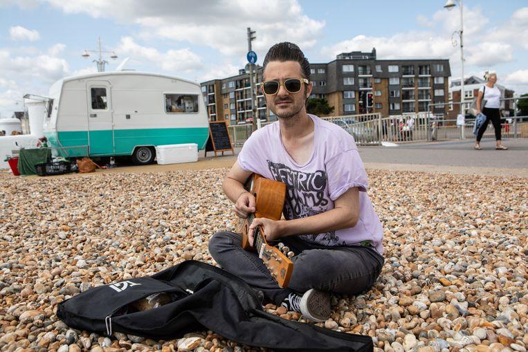 Frankie McGinty, speelt gitaar in de zon op het grindstrand van Bognor Regis. Hij is geen fan van Boris Johnson.  Beeld Antonio Olmos
