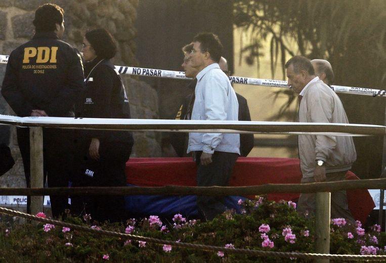 De kist met het stoffelijk overschot van Pablo Neruda wordt weggedragen door forensche experts en familieleden, afgelopen maandag. Beeld epa
