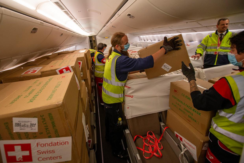 Dozen met beschermingsmiddelen worden uit een passagiersvliegtuig geladen in Genève. Beeld Salvatore Di Nolfi / AP